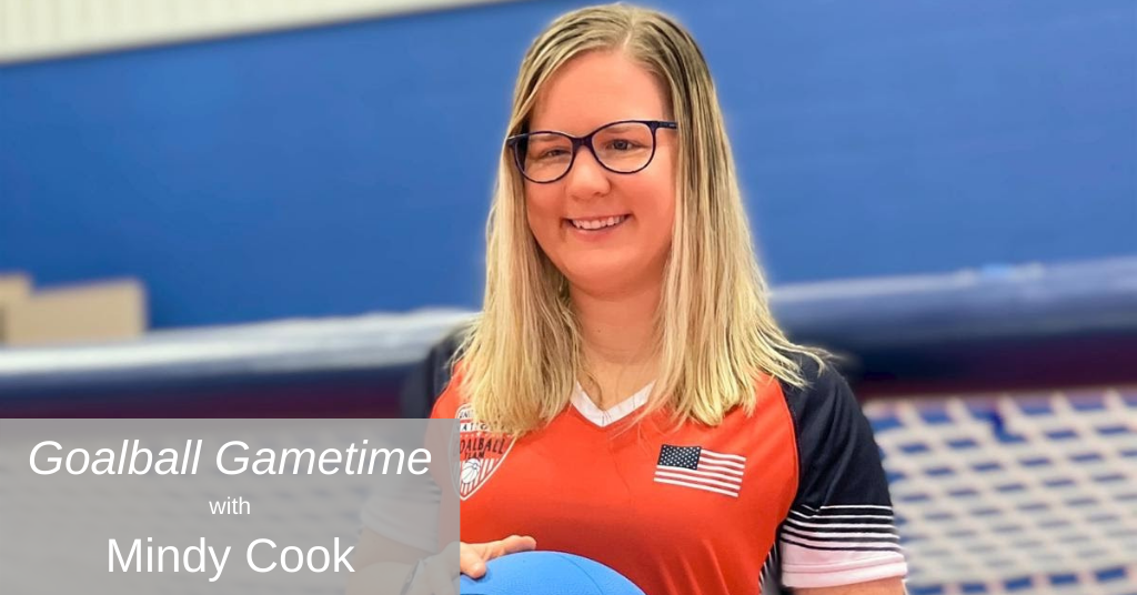 Mindy Cook poses in front of a goalball net holding a goalball and wearing a red USA Goalball shirt.