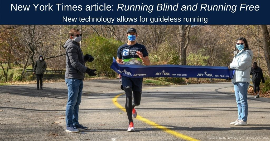 Thomas Panek breaks through a finish line banner held by two people as he completes a run through Central Park in New York City by following a yellow line painted on the pavement that assists the technology he wears on his waist. Thomas is wearing a blue baseball hat, a blue mask and a Guiding Eyes For The Blind t-shirt.
