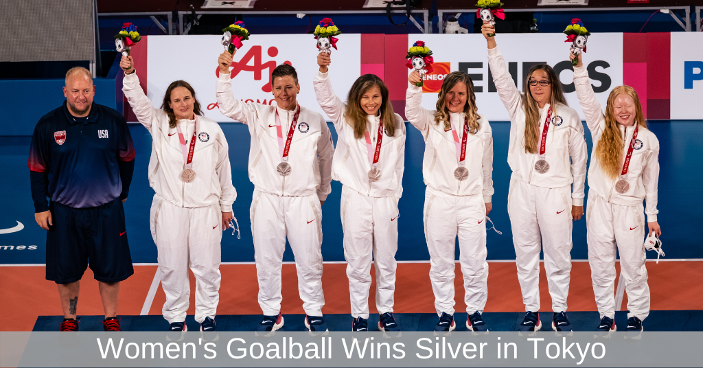 Coach Jake Czechowski stands next to the USA Women\\\'s Goalball Team on the podium after the team received their silver medals. The six athletes are wearing matching white pants and white tops as they hold aloft bouquets of flowers. Next to Coach Czechowski (l to r) is Lisa Czechowski, Asya Miller, Amanda Dennis, Mindy Cook, Eliana Mason and Marybai Huking.