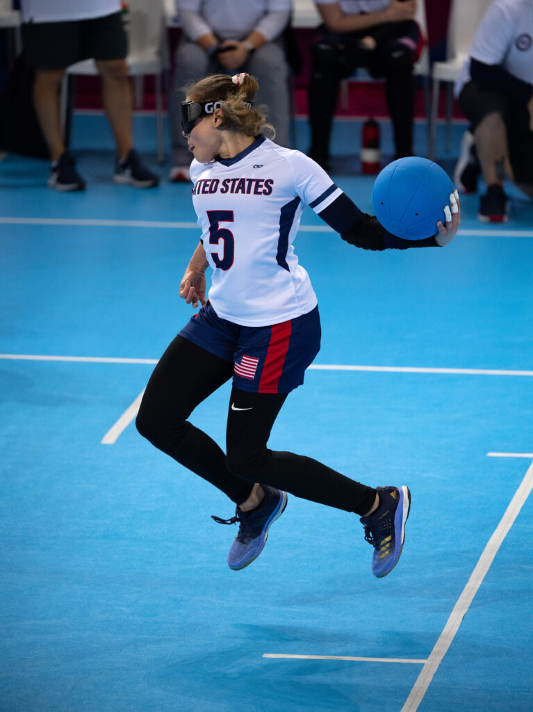"""With both feet off the ground, Amanda Dennis spins in the air as she prepares to unleash a throw during the 2019 Parapan American Games in Lima, Peru. She is wearing a white jersey with number 5 and the words """"United States on the front, as well as blue shorts with the American flag on the left thigh over black tights."""