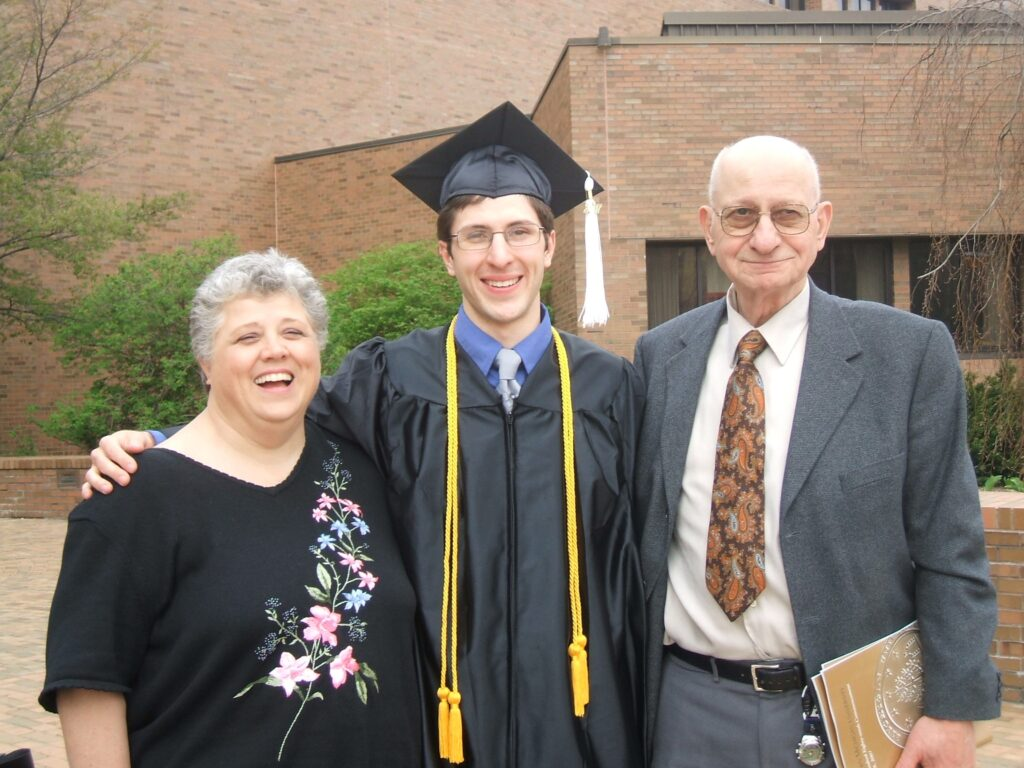 Wearing a graduation cap and gown, John poses with his parents.