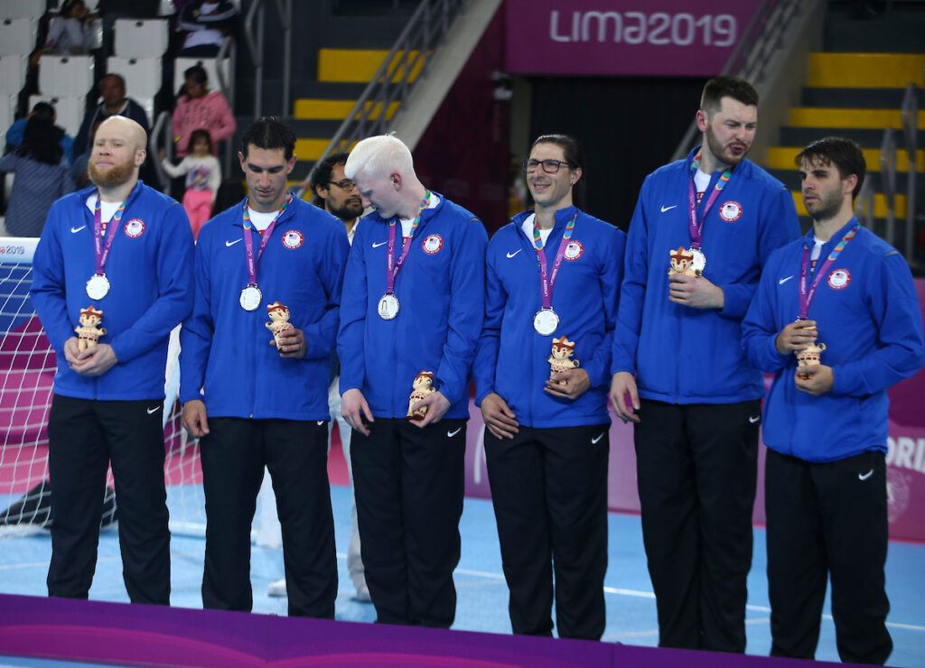 Daryl and his five teammates stand behind the podium with silver medals around their necks during the medal ceremony at the 2019 Parapan American Games in Lima, Peru.