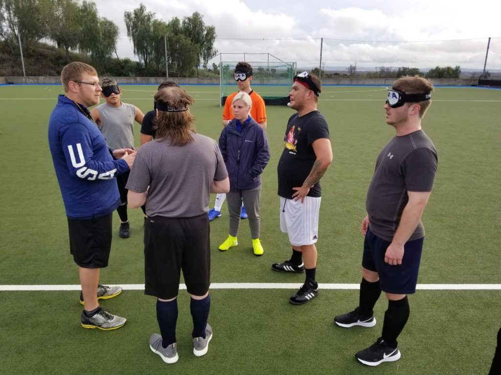 Athletes wearing eyeshades listen to coach Tim Taylor in the middle of the soccer field