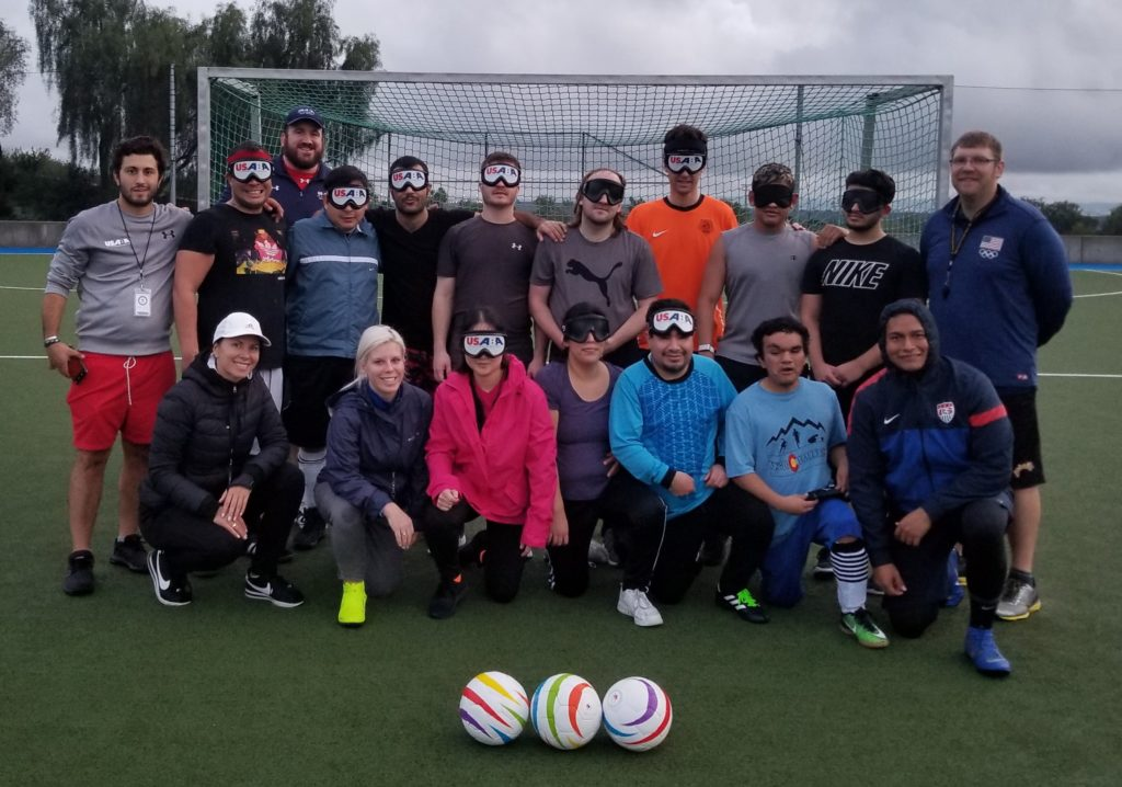 Athletes, coaches and staff pose for a group photo in front of a soccer goal. Three soccer balls are positioned on the ground in front of the group