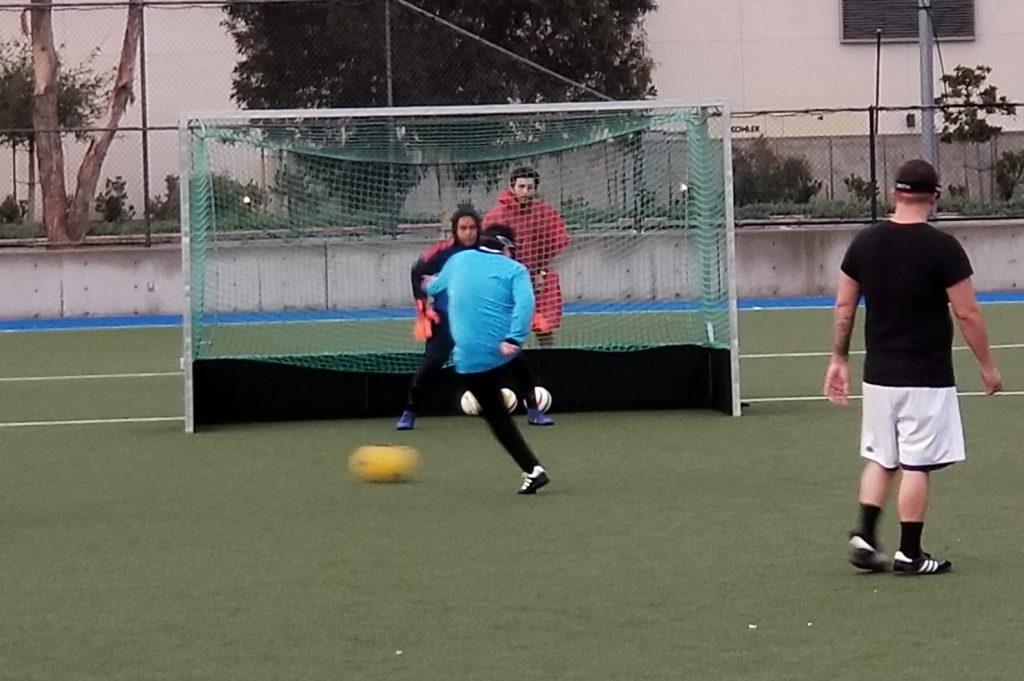 Athlete Alvaro Mora takes a shot on goal as the goalie tries to defend