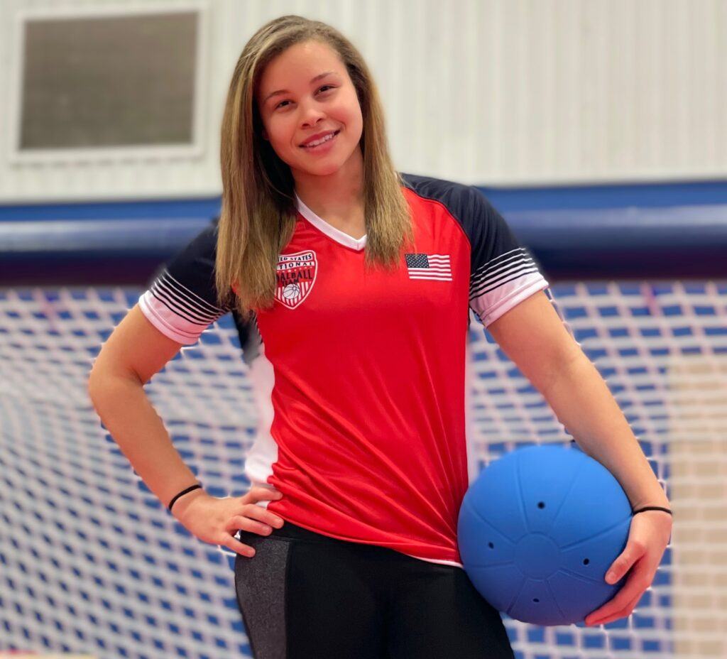 Amanda Dennis poses for a photo in front of a goalball goal. She is wearing a red USA Goalball National Team shirt with an American flag on the chest and is cradling a goalball in her left hand.