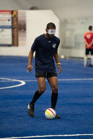 Wearing a blue t-shirt and black eyeshades, Antoine Craig dribbles a soccer ball on a field of blue turf.