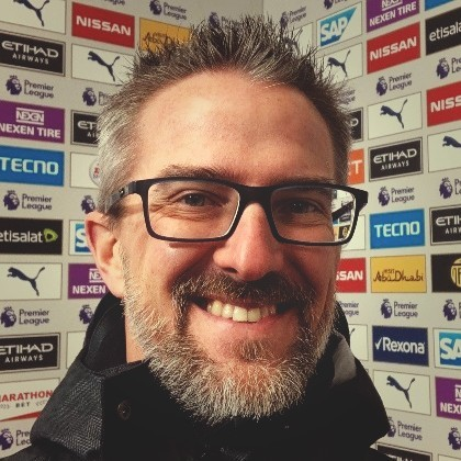 A headshot of Brian Eaton smiling and standing in front of a wall of sponsor logos. Brian sports a beard and is wearing glasses.