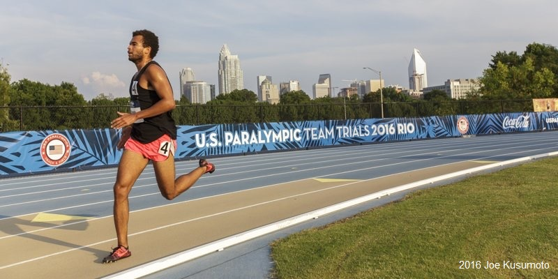 Chaz runs on a blue track with a banner behind him that reads U.S. Paralympic Team Trials 2016 Rio.