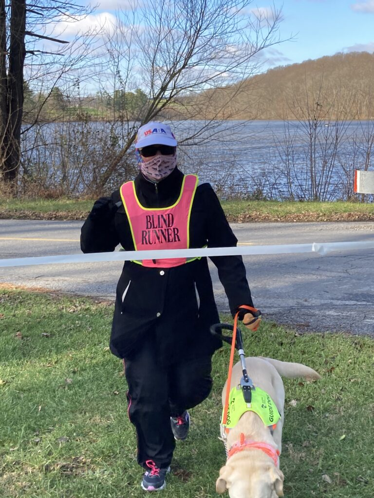 Wearing her USABA hat, a mask and Blind Runner vest, Cindy Lou Altman runs through the tape with her guide dog Jada to finish her 5k run on National Blind Running Unity Day. In the background are trees and a lake.