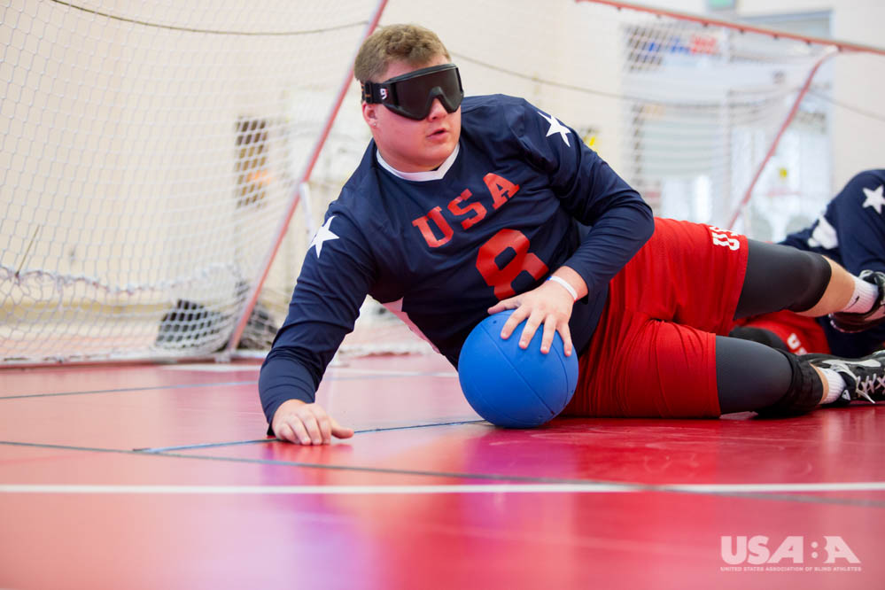 Cody blocking a throw on a red goalball court during practice.