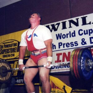 Cody Colchado is shown executing a dead lift with the barbell across the front of his thighs.