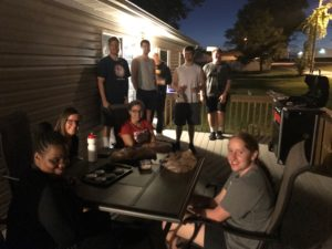Resident goalball players sitting on deck outside a house, some are sitting around a table and some are standing. They are enjoying a cookout.