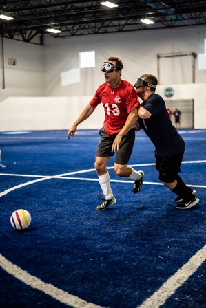 Two players wearing eyeshades battle for the ball with one in a red t-shirt trying to maintain control of the ball while the defender in a blue t-shirt attempts to knock him off the ball.