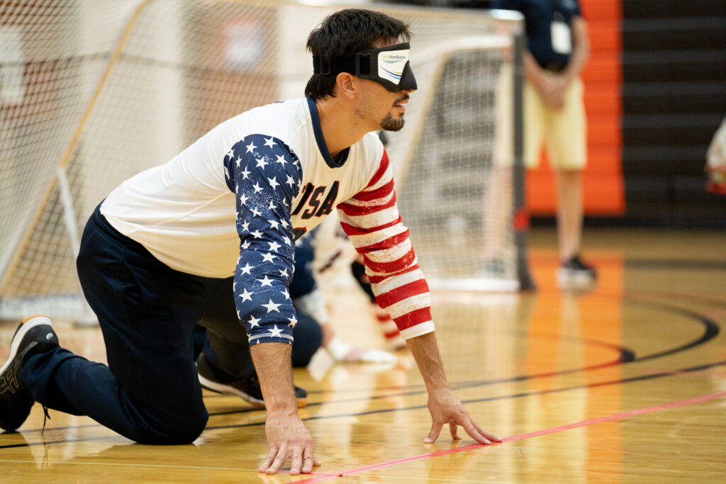 Tyler Merren leans on his right knee with his fingertips touching the floor as he anticipates an opponent's throw during the 2019 IBSA International Goalball Qualifier in Fort Wayne, Indiana. (photo by Julie Larame)