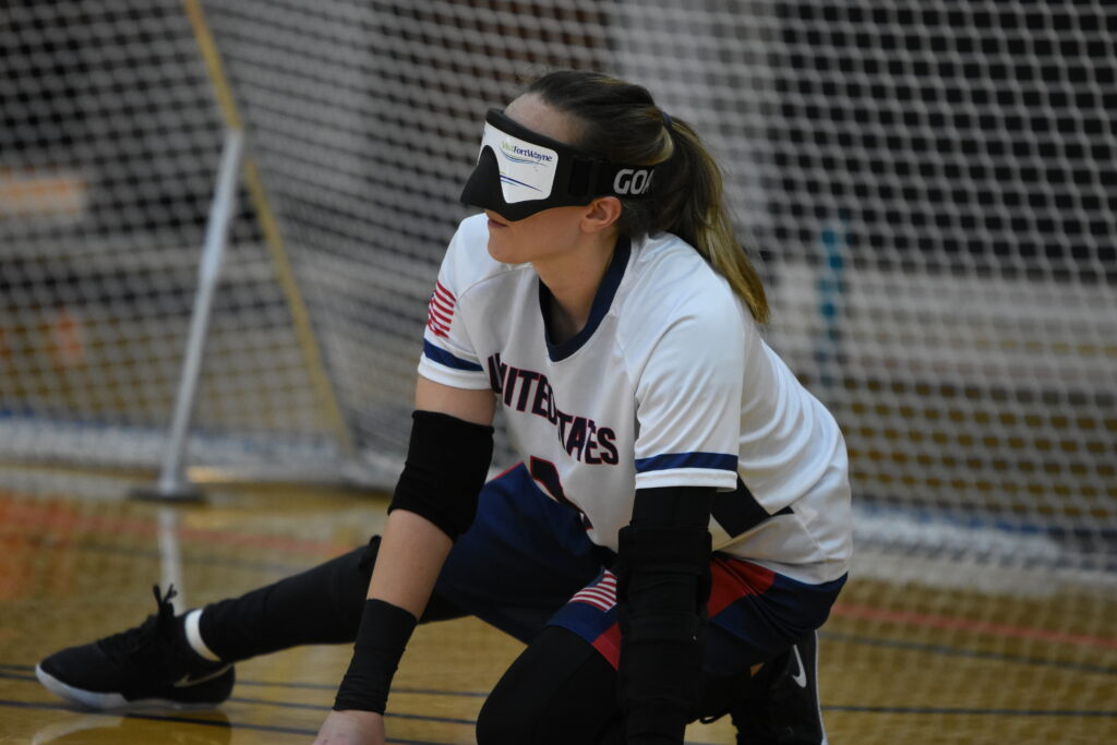 Wearing a white USA jersey and eyeshades, Eliana Mason crouches on the floor in front of her goal, ready to defend an opponent's throw.