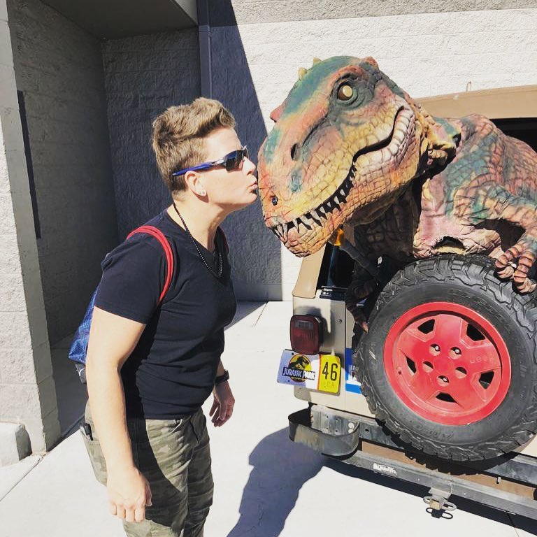 Asya Miller plants a kiss on a replica tyrannosaurus rex sticking out the back of a Jeep with a Jurassic Park license plate.