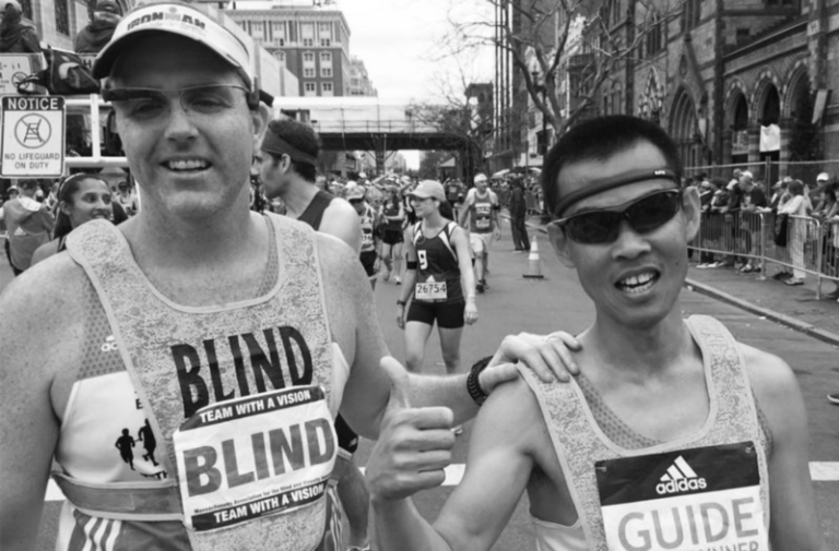 Black and white photo of Erich Manser and his guide. Erich is on the left and has his left hand on the shoulder of his guide who is standing beside Erich wearing sunglasses and giving the camera a thumbs up.