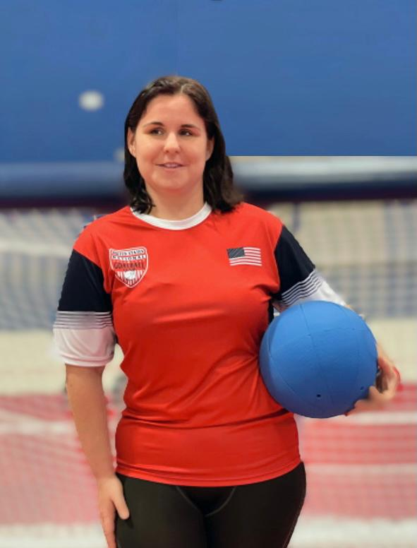 Libby Daugherty poses while holding a goalball in her left hand. She is wearing a red USA Goalball short sleeve shirt with a USA flag on the left chest.