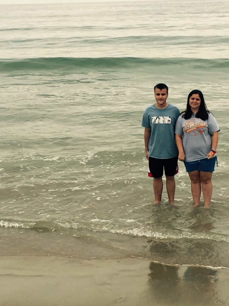 Wearing t-shirts and shorts, Libby and her younger brother Steven face the camera as they stand in the shallow surf off the coast of Maine.