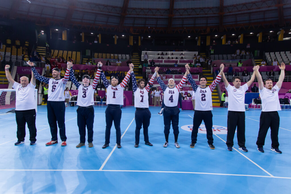 Matt (#7 in middle) raises his arms along with teammates and coaches after the USA Men's Goalball Team clinched a berth in the Tokyo 2020 Paralympic Games at the 2019 Parapan American Games in Lima, Peru.