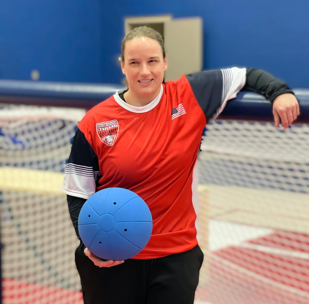 Lisa Czechowski poses in front of a goalball goal with her left arm resting on the crossbar. She is wearing a red USA Goalball jersey and holding a blue goalball in her right hand.