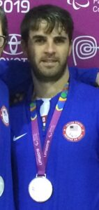 Matt is pictured wearing a silver medal around his neck and a blue United States Parapan Am Team jacket at the 2019 Parapan American Games in Lima, Peru.