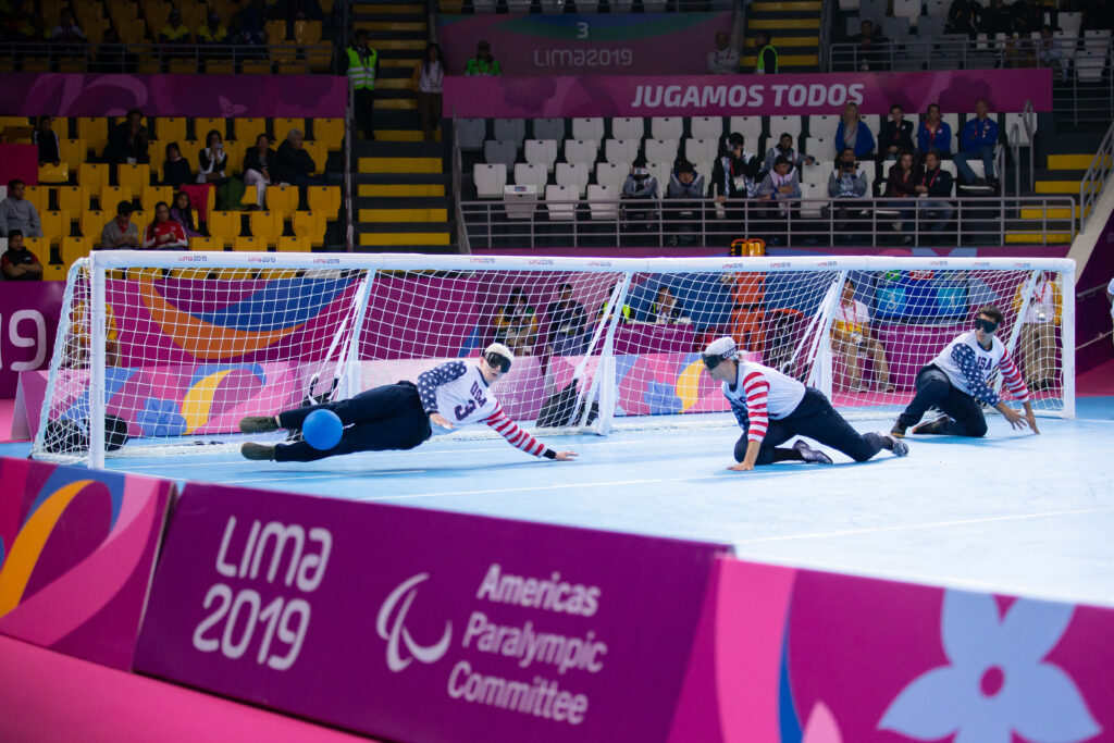 A photo taken from the sidelines at the 2019 Parapan American Games in Lima, Peru, shows Josh Welborn elevating his body horizontally to make a stop with his legs. He is supporting himself on his left hand.