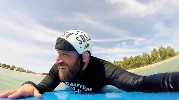 Snapshot of Joshua Loya smiling, paddling on a surfboard.