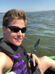 Asya is pictured wearing sunglasses and a life vest while seated in a kayak on a body of water.