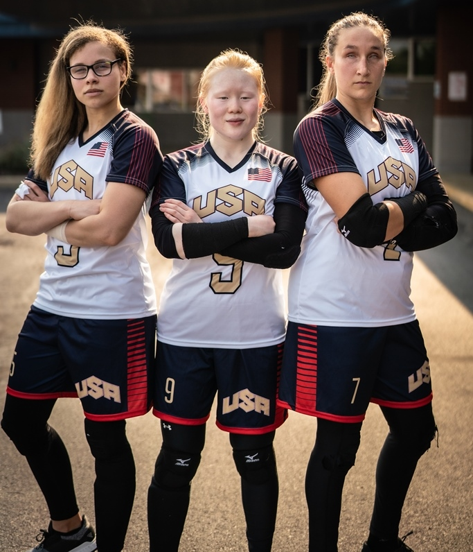 Marybai Huking stands between teammates Amanda Dennis and Eliana Mason. All three have their arms folded with serious expressions on their faces. They are wearing white USA jerseys and blue shorts with gold lettering and numbers.