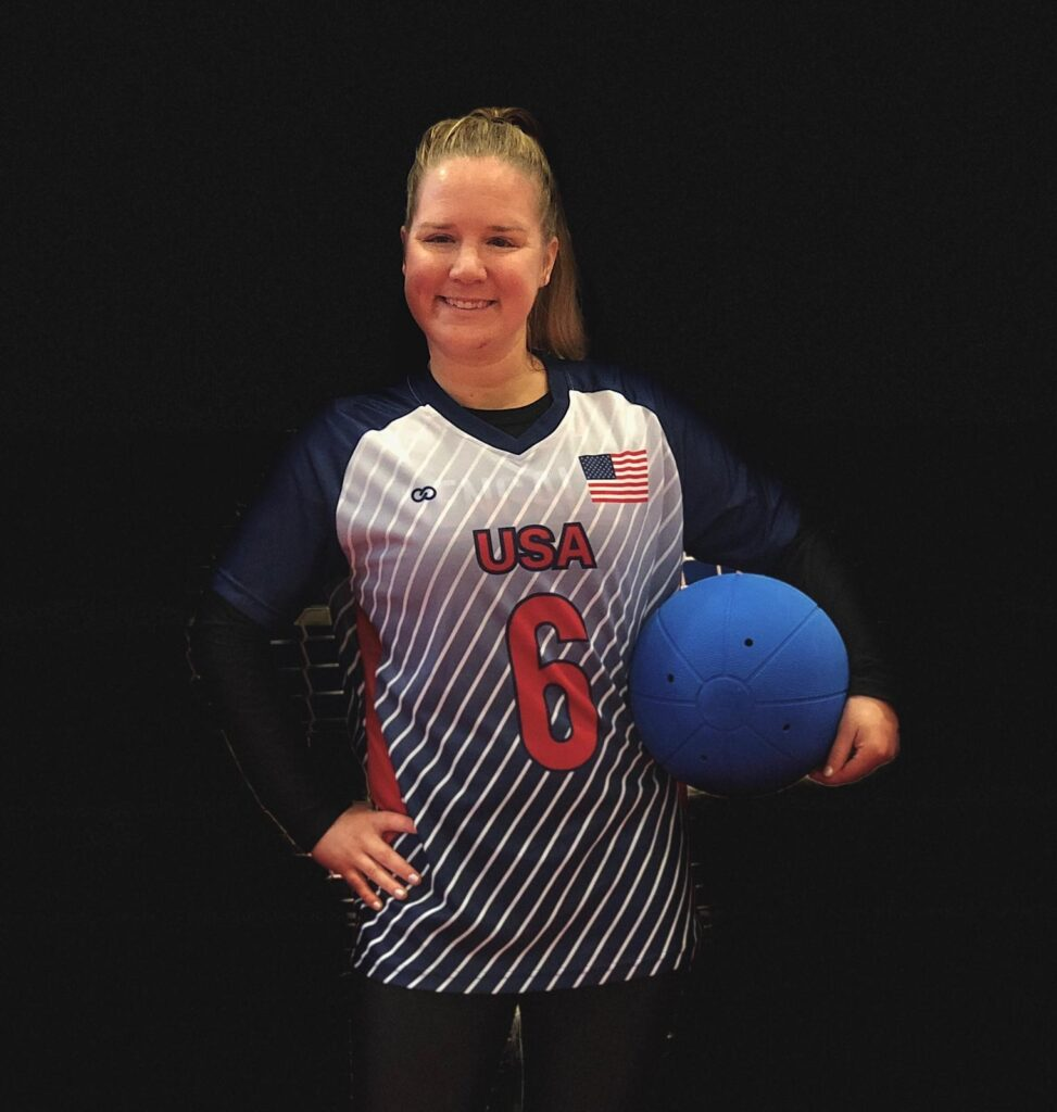 Mindy Cook poses for a photo with a goalball under her left arm. She is wearing a Team USA jersey with #6 on the front.