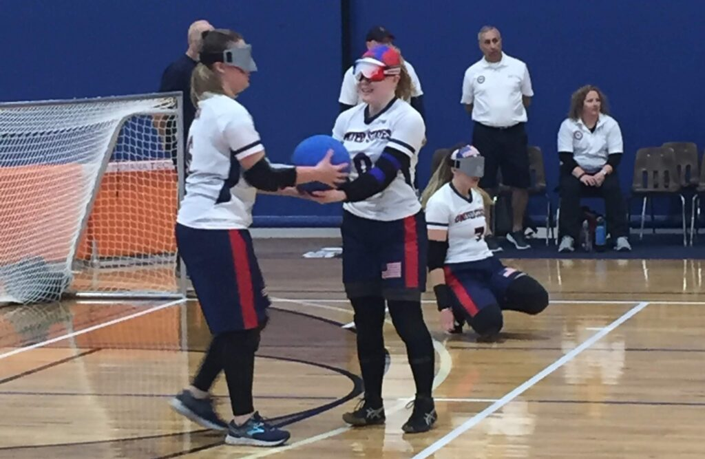Mindy Cook (left) is handed a goalball by teammate Marybai Huking during a competition at Turnstone Center in Fort Wayne, Indiana.