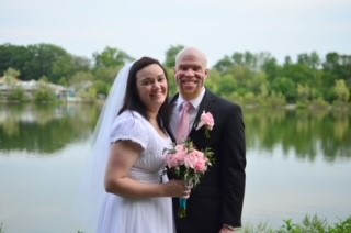 Daryl and his wife Melissa pose in front of a lake on their wedding day. Melissa is wearing a white wedding dress and veil, and Daryl is wearing a dark suit coat, white dress shirt and pink tie.
