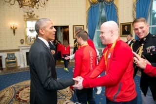 Wearing his red USA Paralympic Team jacket and his silver medal around his neck, Daryl smiles as he shakes hands with President Barack Obama inside the White House after the Rio 2016 Paralympic Games.