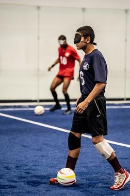 Ricardo Castaneda dribbles a soccer ball across the blue turf. He is wearing dark eyeshades and a blue t-shirt.