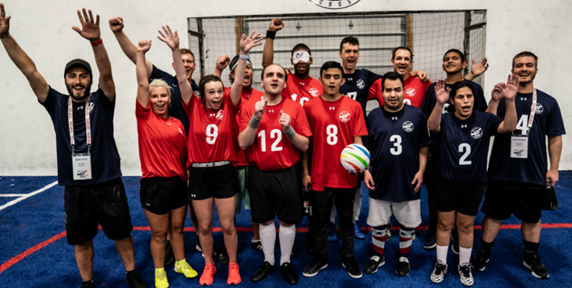 A group photo of players and coaches wearing red and blue t-shirts and shouting for joy at the camera. One player in front holds a soccer ball in his left hand.