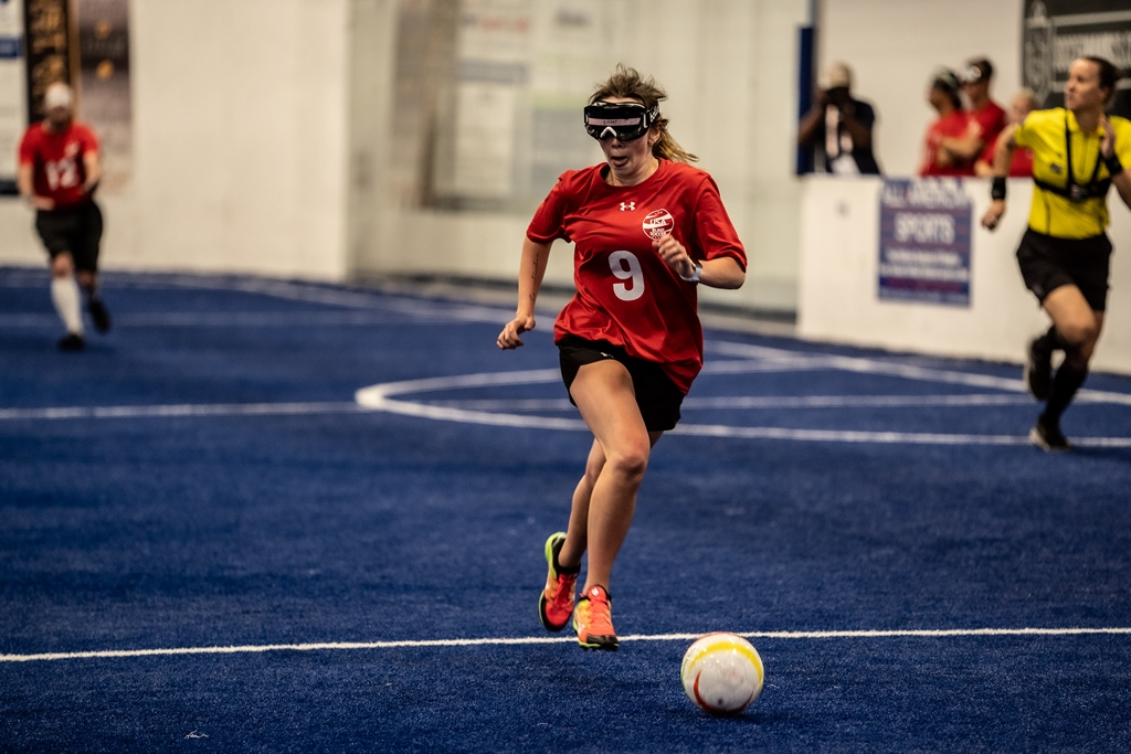 Wearing a red t-shirt and dark eyeshades, Bailey Martin sprints down the blue turf of the soccer pitch as she tracks the soccer ball in front of her.