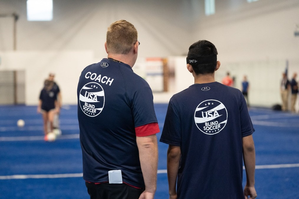 """Seen from behind, coach Tim Taylor gives instruction to a player as they face the soccer field. Both are wearing blue t-shirts with """"Coach"""" printed on the back of Tim Taylor's shirt."""
