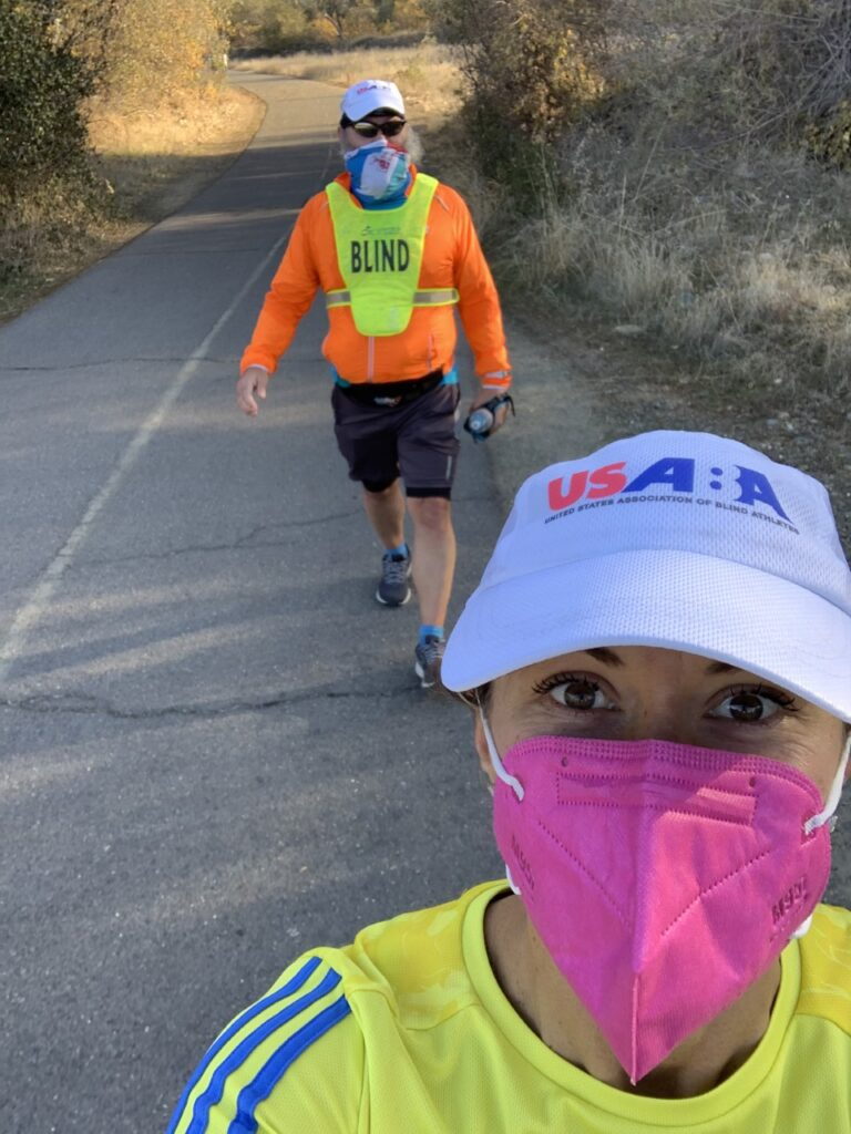 "Rob Sanchas' guide takes a selfie of the two runners on a path. Rob is in the background wearing his yellow bib with the word ""BLIND"" on it. Both runners are wearing masks and USABA running hats."