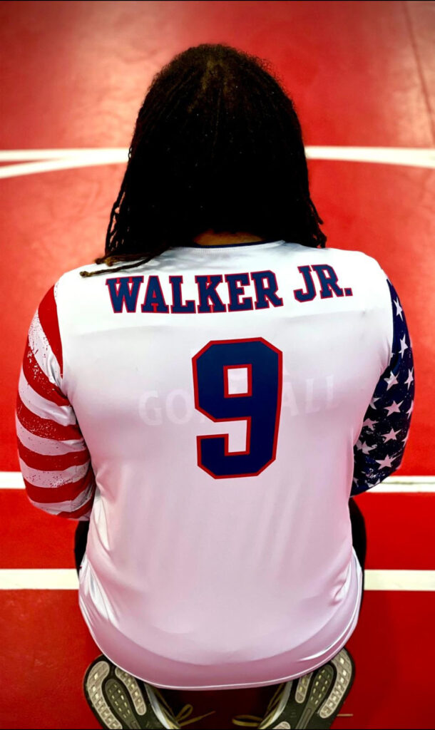 """A photo of Sean Walker's back as he kneels on the floor. The back of his USA jersey has the name """"Walker Jr."""" above the number 9."""