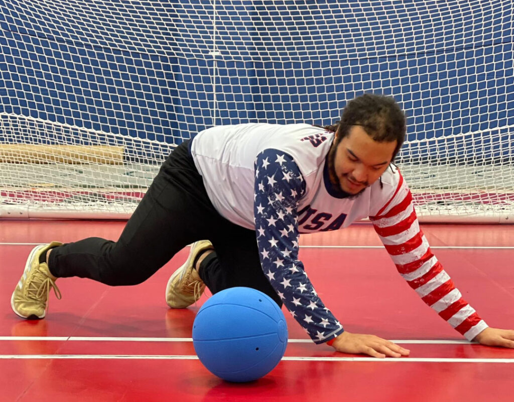 Sean Walker on his hands and knees in front of a goalball goal with a blue goalball in front of him. He is wearing a USA jersey and black pants.