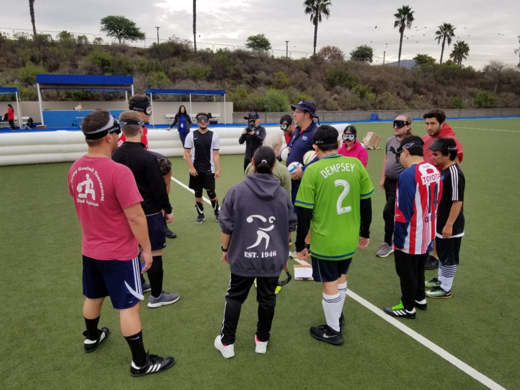 Athletes attending the talent identification camp gather around coach Tim Taylor at midfield of the soccer pitch in Chula Vista, Calif. The athletes are wearing eyeshades and an array of soccer jerseys and competition gear. Palm trees can be seen in the background.