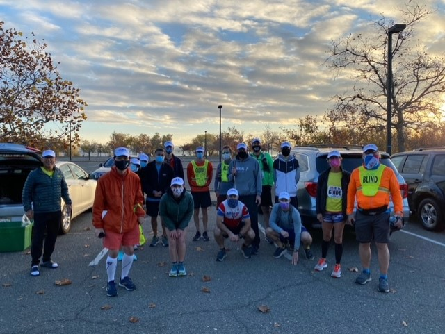 A group of 16 runners and guides wearing masks pose for a group photo in a parking lot. Some are wearing GUIDE or BLIND bibs.