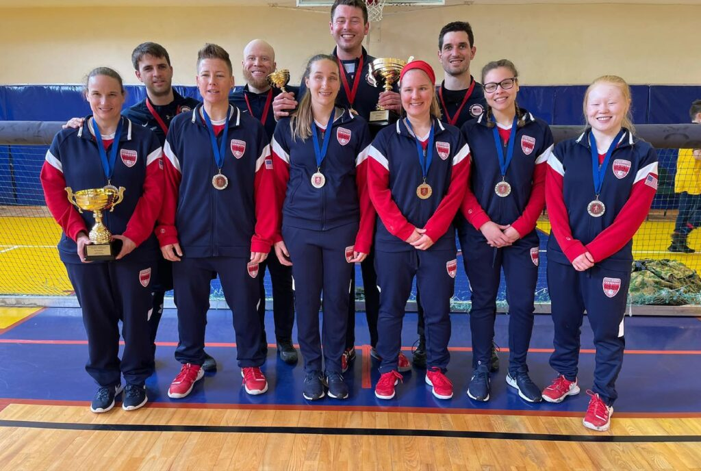 The USA Men's and Women's Goalball Teams pose on the court wearing their medals and holding trophies.