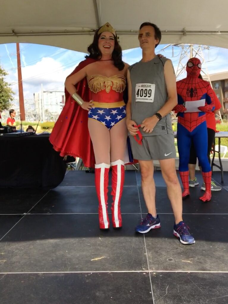 William poses with a woman dressed as Wonder Woman while a man dressed as Spiderman stands in the background during the CASA Superhero 5k. Proceeds of this race go to help protect children who have been abused.
