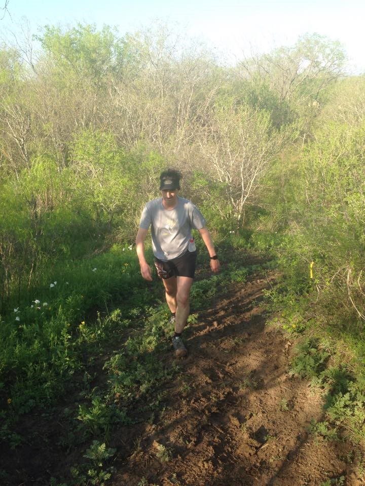 William Greer is shown running on a muddy trail through green trees and bushes during the Prickly Pear 50k. For this race, he came in third place in his age group.