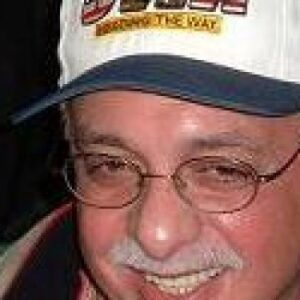 A headshot of Dan Parisi wearing glasses and a baseball hat.