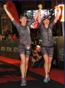 Randi Strunk and her guide finishing the Ironman Texas in 2018. Both have their arms raised in the air, grinning.
